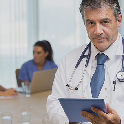 Smiling doctor with tablet at a meeting